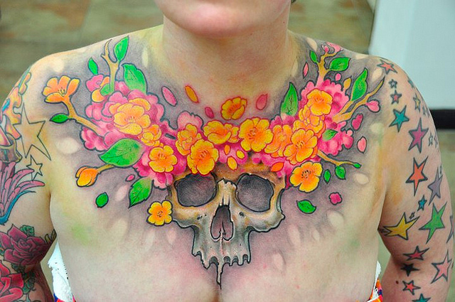 Skull and flowers chest tattoo