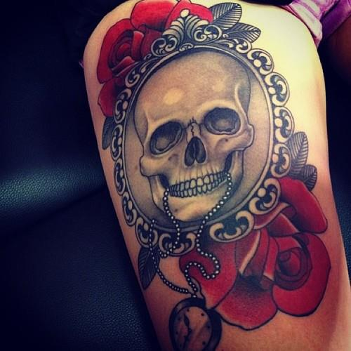 Framed skull and roses thigh tattoo